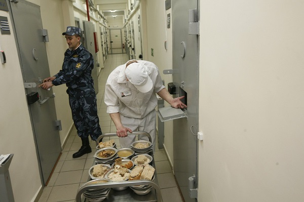 A security officer stands next to an inmate serving dinner to prisoners, inside a zone where especially strict conditions are imposed at a high-security male prison camp outside Russia's Siberian city of Krasnoyarsk May 14, 2013. High-security male prison camp number 17 is intended to house male inmates who are serving a sentence for the first time, and have been convicted for serious crimes. Prisoners at the facility work in wood and metal processing shops, manufacture furniture, sew clothes and do other kinds of work. They can also take part in educational, sport and cultural programs. Picture taken May 14, 2013. REUTERS/Ilya Naymushin (RUSSIA - Tags: CRIME LAW SOCIETY)  ATTENTION EDITORS: PICTURE 12 OF 29 FOR PACKAGE  'INSIDE SIBERIA'S PRISONS'  SEARCH 'ILYA PRISON' FOR ALL IMAGES