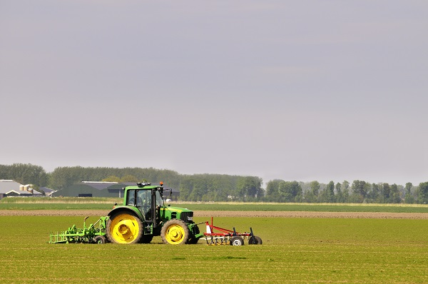 Dronten, The Netherlands - May 14, 2012: John Deere 6430 tractor working the fields near the town of Dronten in Flevoland in spring. A farmer is driving the tractor.