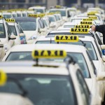 A taxi driver listens to speeches by his colleagues, during an Europe-wide protest of licensed taxi drivers against taxi hailing apps that are feared to flush unregulated private drivers into the market, in front of the Olympic stadium in Berlin. (Thomas Peter/Reuters)