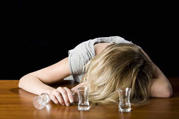 A Young Woman Passed Out Drunk on a Bar Counter --- Image by © Patrick Strattner/fstop/Corbis